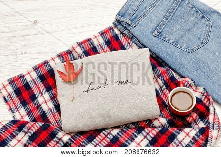 Gray sweater with an inscription plaid jeans coffee mug and autumn leaves. Fashionable concept