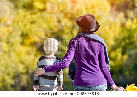 Blond Boy With His Mother In The Hat Sitting On The River Bank. Back View