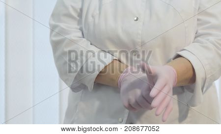 Close-up - unidentified woman doctor puts on surgical gloves for medical operations