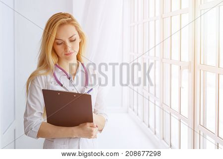 Woman Doctor Holding Pen Writing On Clipboard For Taking Patient Treatment