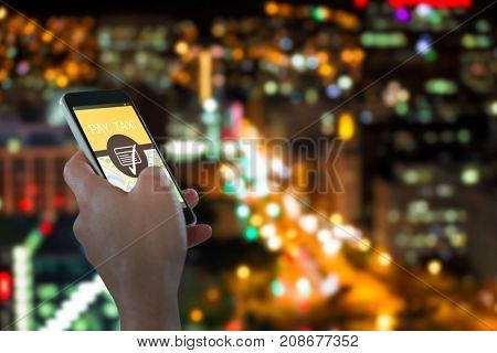 Close-up of hand holding mobile phone against defocused image of illuminated buildings