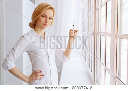 Young Beautiful Women Doctor With Syringe. Medicine And Health Care Concept.