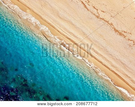 Top view of a deserted beach. The greek coast of the Ionian Sea. Aerial photo of sea waves reaching shore.