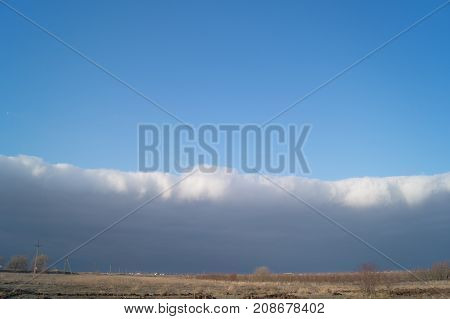 Dark horizontal cloud under the prairie at sunset