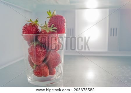 Glass full of red ripe strawberries stands on the shelf of fridge