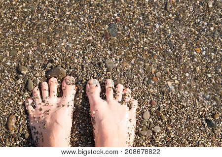 Vacation concept. Sandy woman feet on the beach and sand