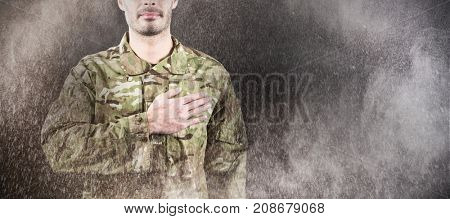 Mid section of soldier taking oath against black wall