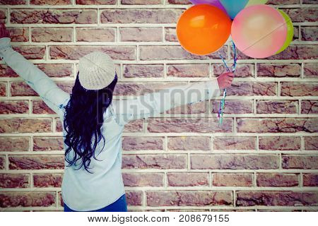 Full length rear view of carefree woman holding colorful balloons against image of a wall