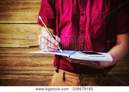 Mid section of student with mobile phone writing on notebook  against wooden background