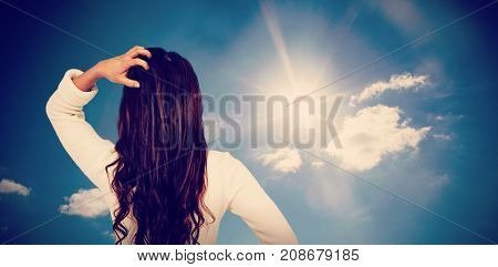 Rear view of confused woman with hand in hair  against cloudy sky with sunshine