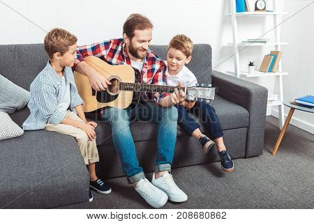 happy father with cute little sons playing guitar at home