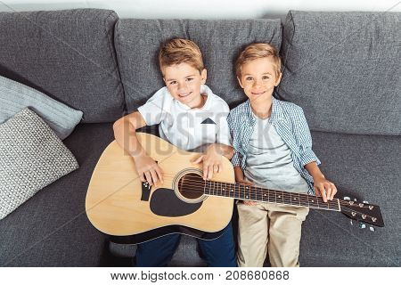 high angle view of adorable little brothers with guitar smiling at camera while sitting on sofa at home