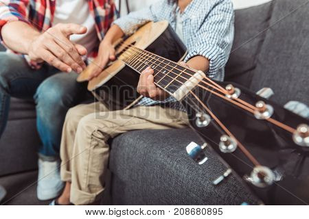 close-up partial view of father and son playing guitar together