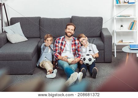 father with sons eating popcorn while watching soccer match at home