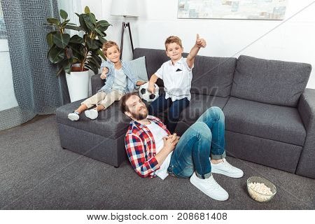 cute little boys with soccer ball showing thumbs up while spending time with father at home