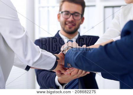 Business people group happy showing teamwork and joining hands or giving five after signing agreement or contract in office, close-up.
