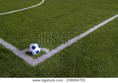 Soccer football in corner of artificial grass field with copy spaces. Corner kick is for restarting play when ball goes out over goal line without score and last touched by defender.