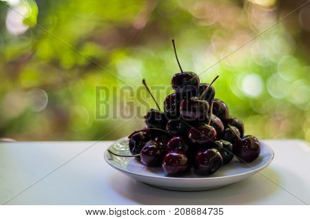 closeup pile of dark cherry on white plat on white table with green bokeh background. cherries are nutritious source for helping you get your daily amount of fruit. high in fiber vital vitamin c.