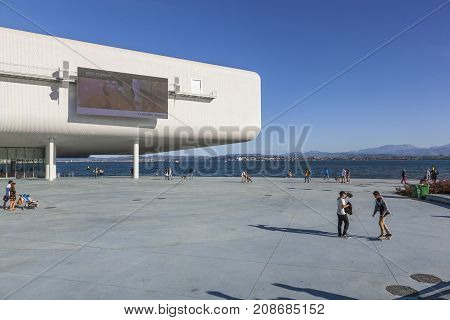 SANTANDER SPAIN - OCTOBER 7 2017: Tourists and local citizens stroll on the promenade near the Centro Botin. The building was designed by Italian architect Renzo Piano.