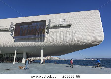 SANTANDER SPAIN - OCTOBER 7 2017: Tourists and local citizens strolling on the promenade near the Centro Botin. The building was designed by Italian architect Renzo Piano.