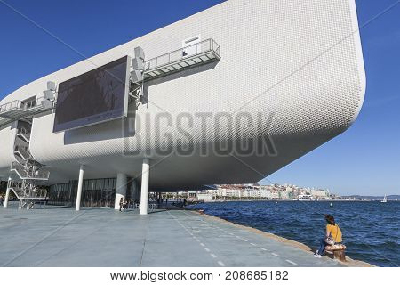 Santander Spain - OCTOBER 7 2017: Families and young adults enjoy the friendly weather next to the Centro Botin. The building was designed by Italian architect Renzo Piano.