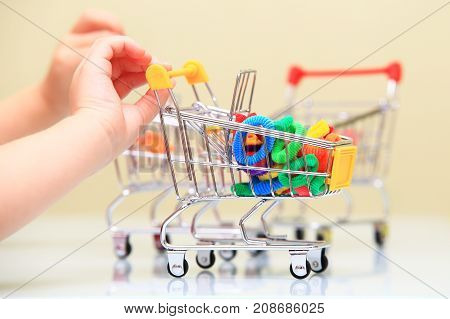 Baby accessorize selling theme. Child hand hold small shopping trolley with hair band.