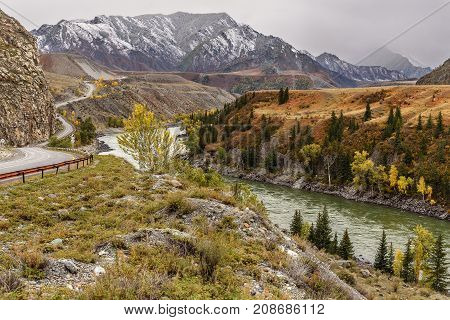 A colorful autumn landscape with a winding asphalt road along the river mountains covered with first snow and a river on the background of the cloudy sky