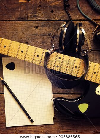Music concept image vintage guitar with old used headphones on a rustic wooden background Jazz rock or blues music concept