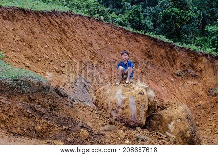 A Boy Sitting On Rock In Sapa, Northern Vietnam