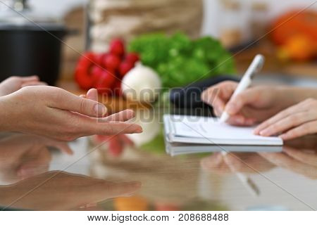 Close-up of human hands are gesticulate over a table in the kitchen. Women choosing menu or making online shopping. So much ideas for tasty cooking.