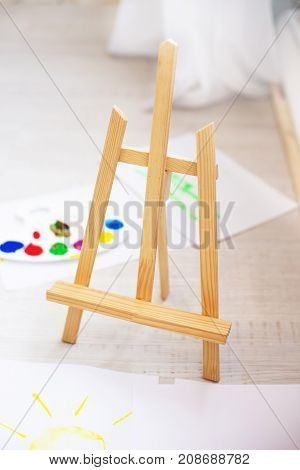 Wooden easel with artist color palette and paper with drawn the sun lying on the floor