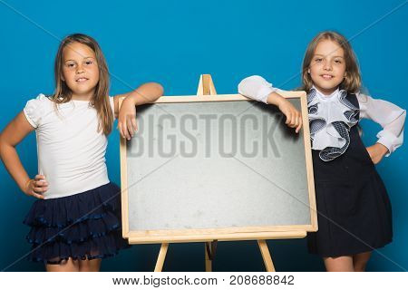 Children lean on blackboard copy space. Education and school concept. Schoolgirls with smiling faces stand near blackboard. Girls in school uniform on blue background.