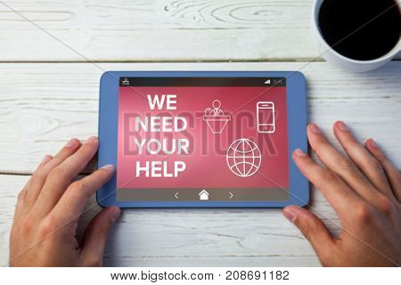 We Need your Help text with various icons on screen against hands using tablet on desk