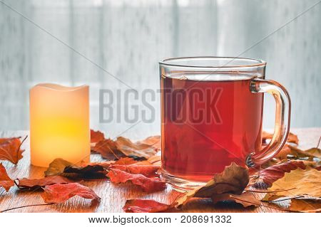Glass cup of tea and glowing candle on wooden table with autumn leaves. Warm toning. Light tulle background