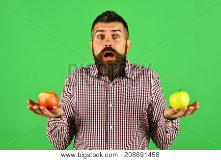 Farmer With Surprised Face Decides Between Two Fresh Fruit.