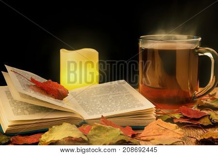 Glass cup of hot tea glowing candle and opened book on table with autumn leaves. Dark background. Toned