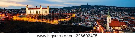 Bratislava Slovakia. Aerial view of the castle and illuminated historical buildings with car traffic and river in the capital of Slovakia Bratislava
