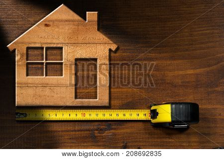 Wooden model house on a wooden table with a tape measure. Construction industry concept