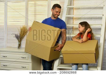 Daughter And Father Hold Boxes And Unpack. Moving And Family