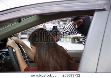 Robber holding a gun to the head for robbery car owner /Screaming Asian woman /Criminal and car thief concept