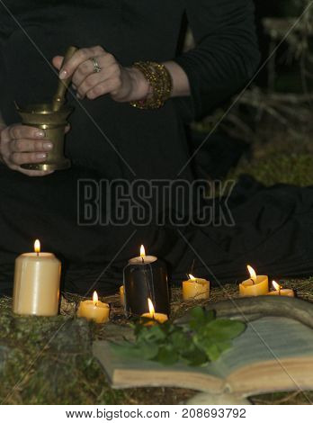 women's hands pestle something in a mortar in front of burning candles a book and collected herbs in the dark