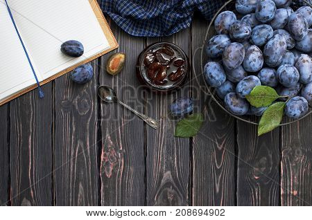 Homemade plum jam in a glass jar and fresh blue plums in a bowl on a dark rustic wooden background with copy space top view.