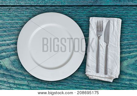 Empty plate and cutlery on petrol colored wood.