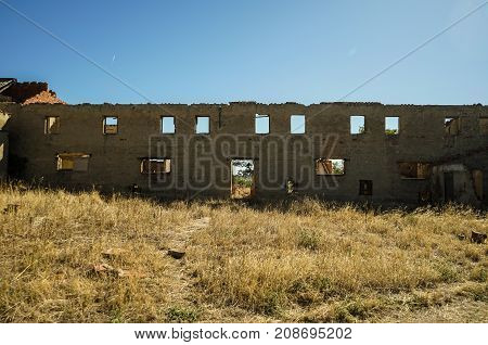 Wall with windows and door in ruins
