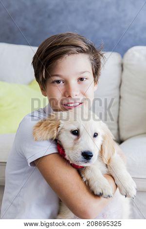 Cute Teen Boy With Baby Retriever Dog In Room