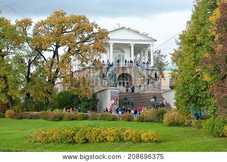 TSARSKOYE SELO, SAINT-PETERSBURG, RUSSIA - OCTOBER 7, 2017: People in The Cameron Gallery Ensemble (the Cameron Thermae) in The Catherine Park. Hercules statue. Autumn view