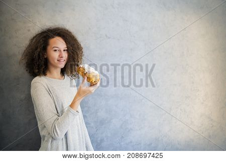 Cure Curly Hair Girl Eating Croissant Against Wall