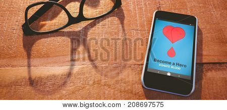 Become a Hero text with heart shape on screen against close up view of smartphone and glasses