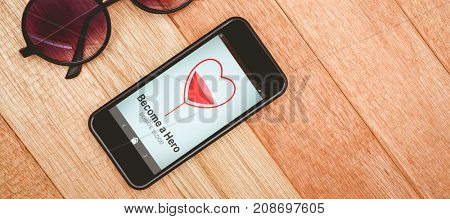 Become a Hero text with heart shape on screen against view of glasses and a smartphone