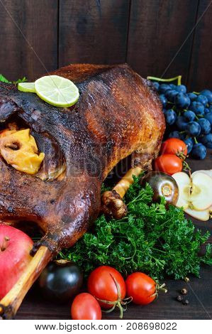 Goose baked in the oven with apples and grapes. Christmas goose on a wooden background. Festive dish.